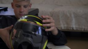 The boy takes game helmet. Blond boy in black windbreaker takes yellow game helmet and going to put it on head. Young gamer spends time at home stock video footage
