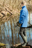 Blond boy in blue jacket and gloves fishing Stock Photo