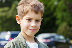 Blond boy in car park. Outdoor portrait of a cheerful blond boy Royalty Free Stock Images