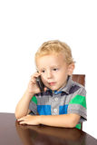 Blond boy careful talking on a cell phone Stock Photos