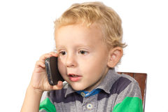 Blond boy careful talking on a cell phone. With a pointed glance stock photos