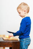 Blond boy child kid preschooler with kitchen knife cutting fruit apple Stock Photos