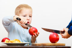 Blond boy child kid preschooler with kitchen knife cutting fruit apple Royalty Free Stock Image