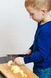 Blond boy child kid preschooler with kitchen knife cutting fruit apple. At home. Happy childhood Stock Images