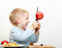 Blond boy child kid preschooler with kitchen knife cutting fruit apple royalty free stock images
