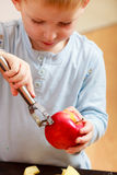 Blond boy child kid preschooler peelings fruit apple at home. Happy childhood Stock Photography
