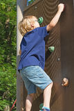 The blond boy climbs the climbing wall. Stock Image
