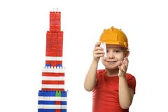 Blond boy in construction helmet and red t-shirt builds a skyscraper from the details of the designer. Isolate on white background.  royalty free stock image