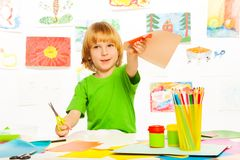 Blond boy cutting color paper Royalty Free Stock Photos