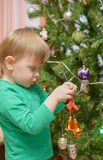 Blond boy decorates Christmas tree Royalty Free Stock Image