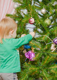 Blond boy decorates Christmas tree Royalty Free Stock Photos