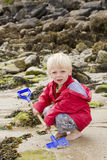 Blond boy digging with spade Royalty Free Stock Image
