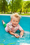 Blond boy draw with calk Royalty Free Stock Images