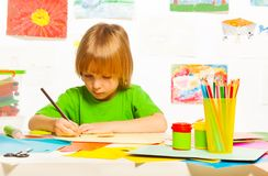 Blond boy drawing. Little 4 years old boy drawing with pencil on the art class Royalty Free Stock Photography