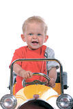 Blond boy driving a toy car. Little blond boy driving a  yellow toy car Stock Photo