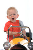 Blond boy driving a toy car. Little blond boy driving a  yellow toy car Stock Photography