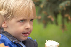 Blond boy eating ice cream Stock Images