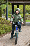 Blond boy enjoying bicycle ride. Smiling boy on a bicycle in a park Royalty Free Stock Image