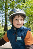 Blond boy enjoying bicycle ride. Smiling boy on a bicycle in a park Stock Images