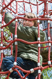 Blond boy enjoying outdoor playground. Cheerful blond boy climbing on cables at playground Stock Photo