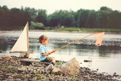 A little boy is fishing on the lake in sammer. Blond boy  fishing on the lake. He is sitting on a raft with a sail in summer day Royalty Free Stock Image