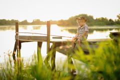 A boy is sitting around the bonfire by the river at night. stock photo