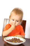 Blond boy greedily eats nuts Royalty Free Stock Image