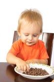 Blond boy greedily eats nuts Royalty Free Stock Image
