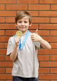 Blond boy is happy gold medal - champion Stock Photo