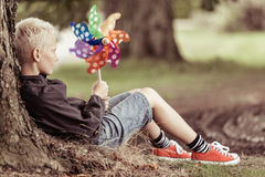 Blond boy holding colorful whirligig sits by tree Stock Photo