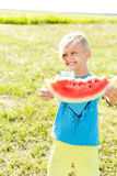 Blond boy holds a watermelon slice in his hands. The boy is eating a watermelon Royalty Free Stock Photo