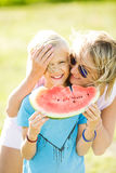 A blond boy holds a watermelon slice in his hands. The boy is eating a watermelon. Royalty Free Stock Photography
