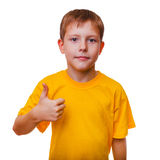 Blond boy kid in yellow shirt holding a thumbs-up, Stock Images