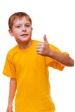 Blond boy kid in yellow shirt holding a thumbs-up, Royalty Free Stock Photography