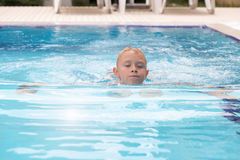 A blond boy learning to swim royalty free stock images