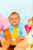 Blond boy looks straight and sit with other pupils Stock Photo