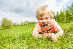 Blond boy with magnifier laying on the green grass Stock Photography