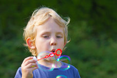 Blond boy making soap bubbles outside Stock Photography