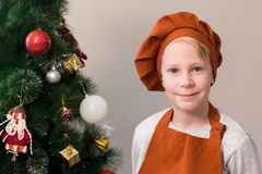 A blond boy in orange cook clothes, stands near the decorated Christmas tree and smiles. Portrait. royalty free stock photo