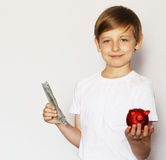 Blond boy with a pig piggy bank Stock Photos