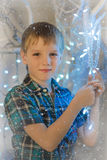Blond boy in a plaid shirt with a glowing Christmas garland Royalty Free Stock Photos