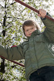 Blond boy at playground. Cheerful blond boy holding a cable at playground Royalty Free Stock Images