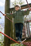 Blond boy at playground. Cheerful blond boy holding a cable at playground Royalty Free Stock Image