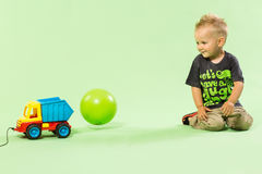 Blond boy playing with colorful car toy green background. Plastic toy Royalty Free Stock Images