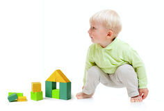 Blond boy playing at floor with building blocks Royalty Free Stock Photos