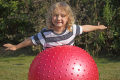 Blond boy is playing with gymnastic ball. Attractive blond boy is playing with red gymnastic ball outdoors Stock Photography