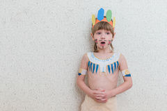 Blond boy playing injun Stock Photo