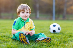 Blond boy of 4 playing soccer with football on football field Stock Image