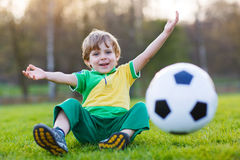 Blond boy of 4 playing soccer with football on football field Royalty Free Stock Photos