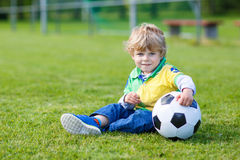 Blond boy of 3 playing soccer with football on football field Royalty Free Stock Image
